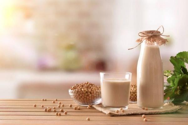 Sữa đậu nành có thành phần tự nhiên, chứa ít calo và nhiều carbohydrate tốt. Chai sữa đậu nành, cốc sữa, hai bát hạt đậu nành